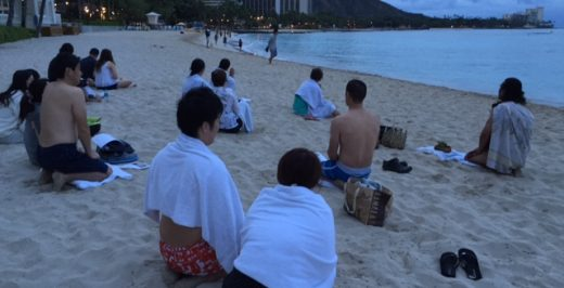 group of people sitting near body of water during daytime