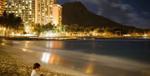 boy sitting on sand near body of water during nighttime