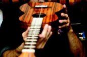 man holding ukulele in room