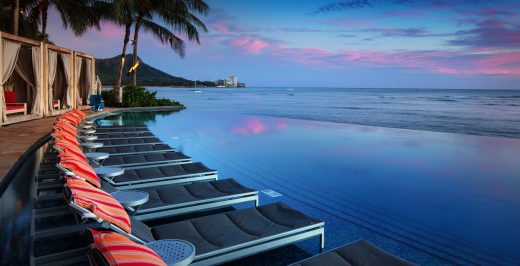 black chaise lounges near body of water