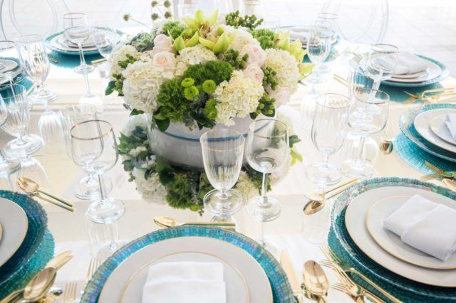 clear footed glasses near white plates on table
