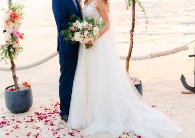 married couple standing on the beach with flower petals on the ground and a bright bouquet in hand