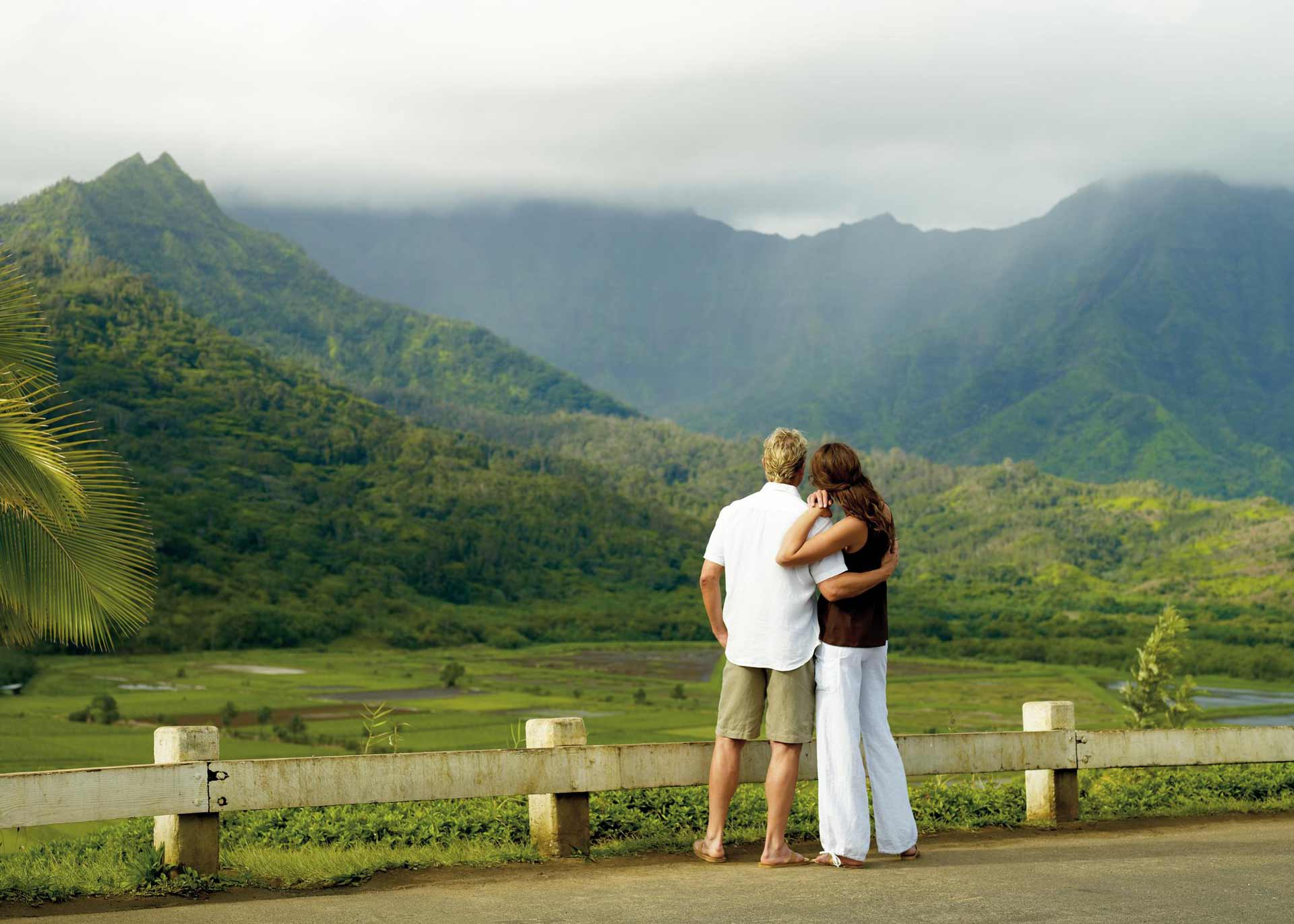 man and woman standing while looking to mountains during daytime