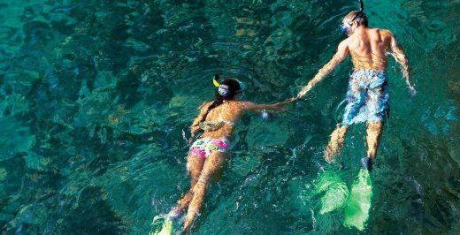man and woman snorkeling in body of water while holding hands