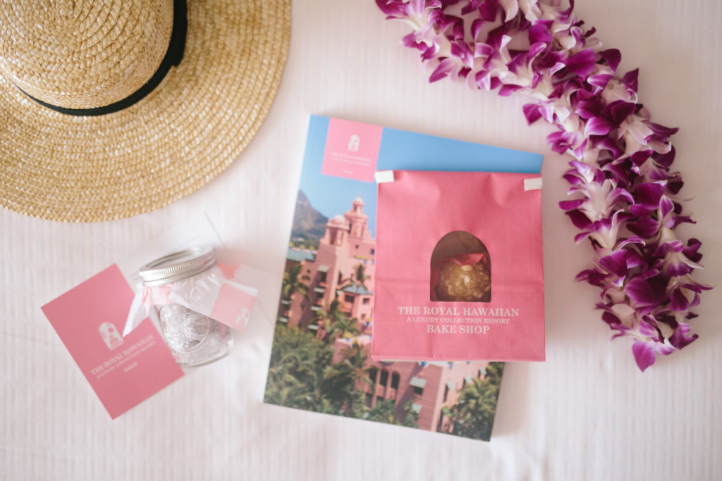 flat-lay photography of The Royal Hawaiian poster beside moth orchid