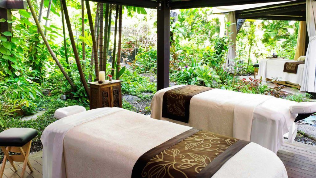 two white massage beds near plants