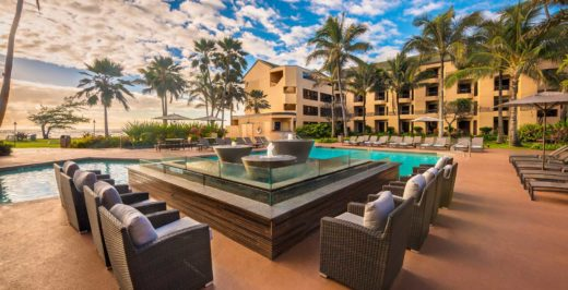 outdoor seating area at pool surrounded by palm trees in hawaii during sunset