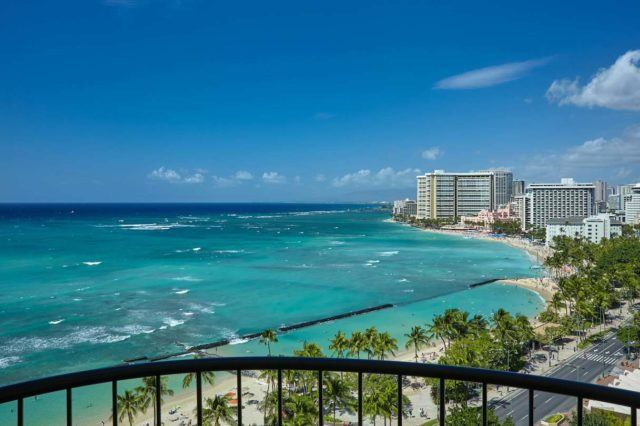 View of the turquoise Pacific Ocean and Waikiki beach from the balcony of a luxury hotel room.
