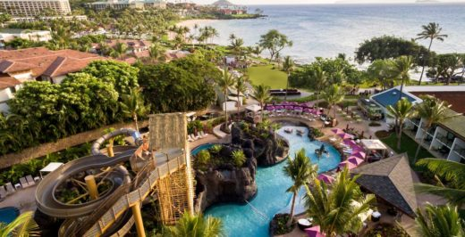 Aerial view of the NALU Adventure Pool at the Wailea Beach Resort – Marriott, Maui with tall winding waterslides, crystal blue pool, and a beautiful beach in the background.