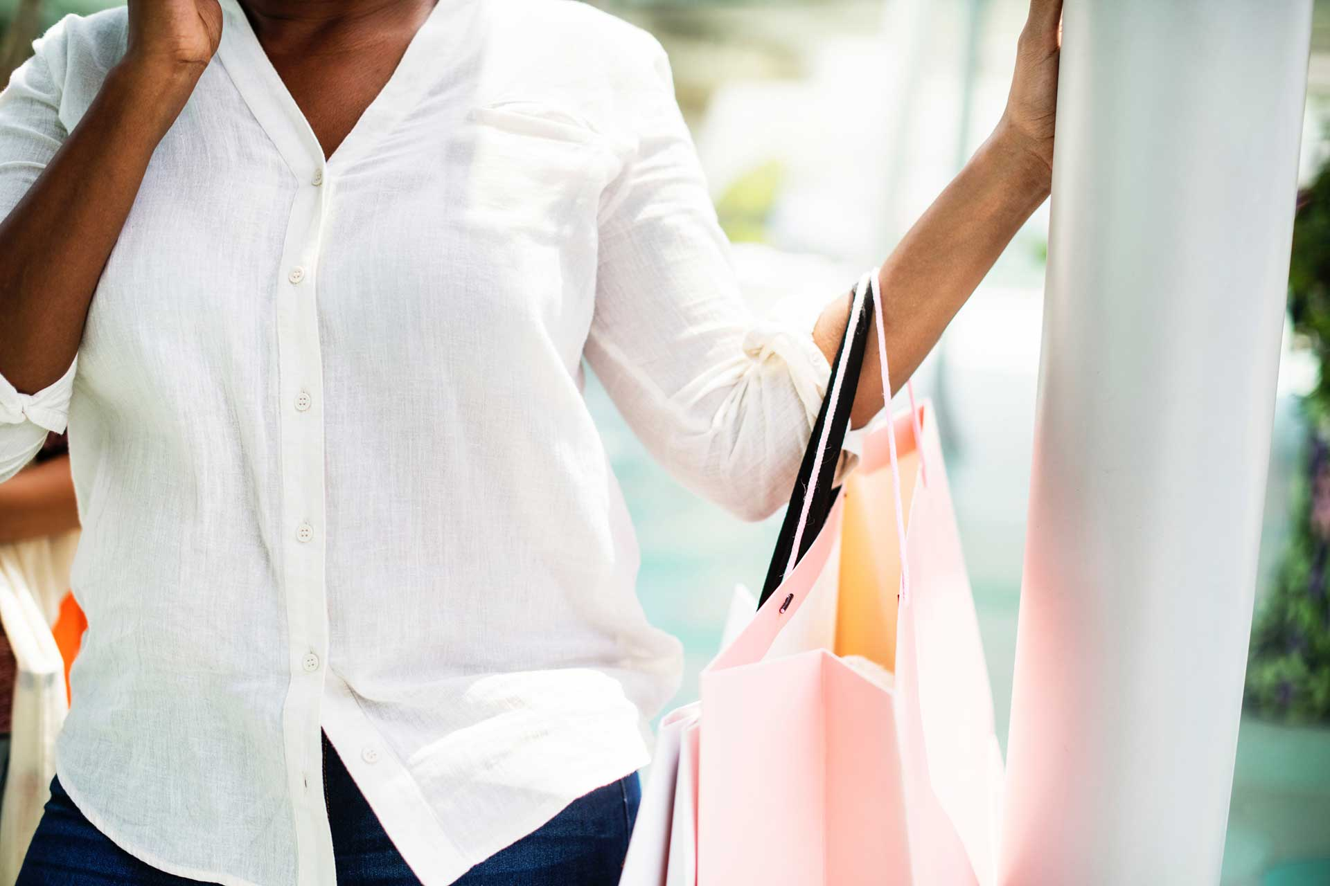 woman in white button-up long-sleeved shirt standing holding pink paper bag