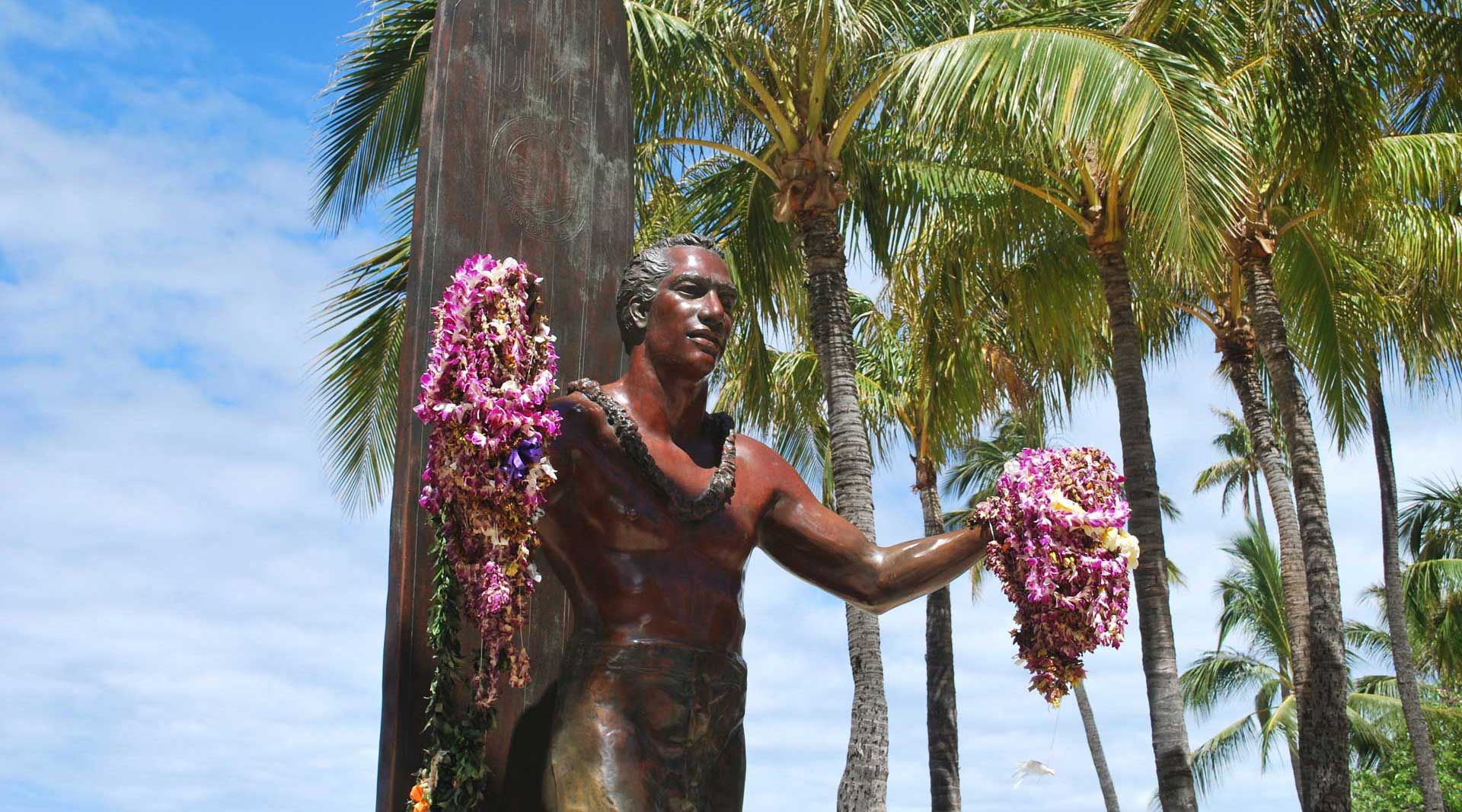 man holding garlands statue near coconut trees