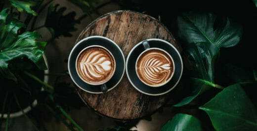 two coffee latte on log