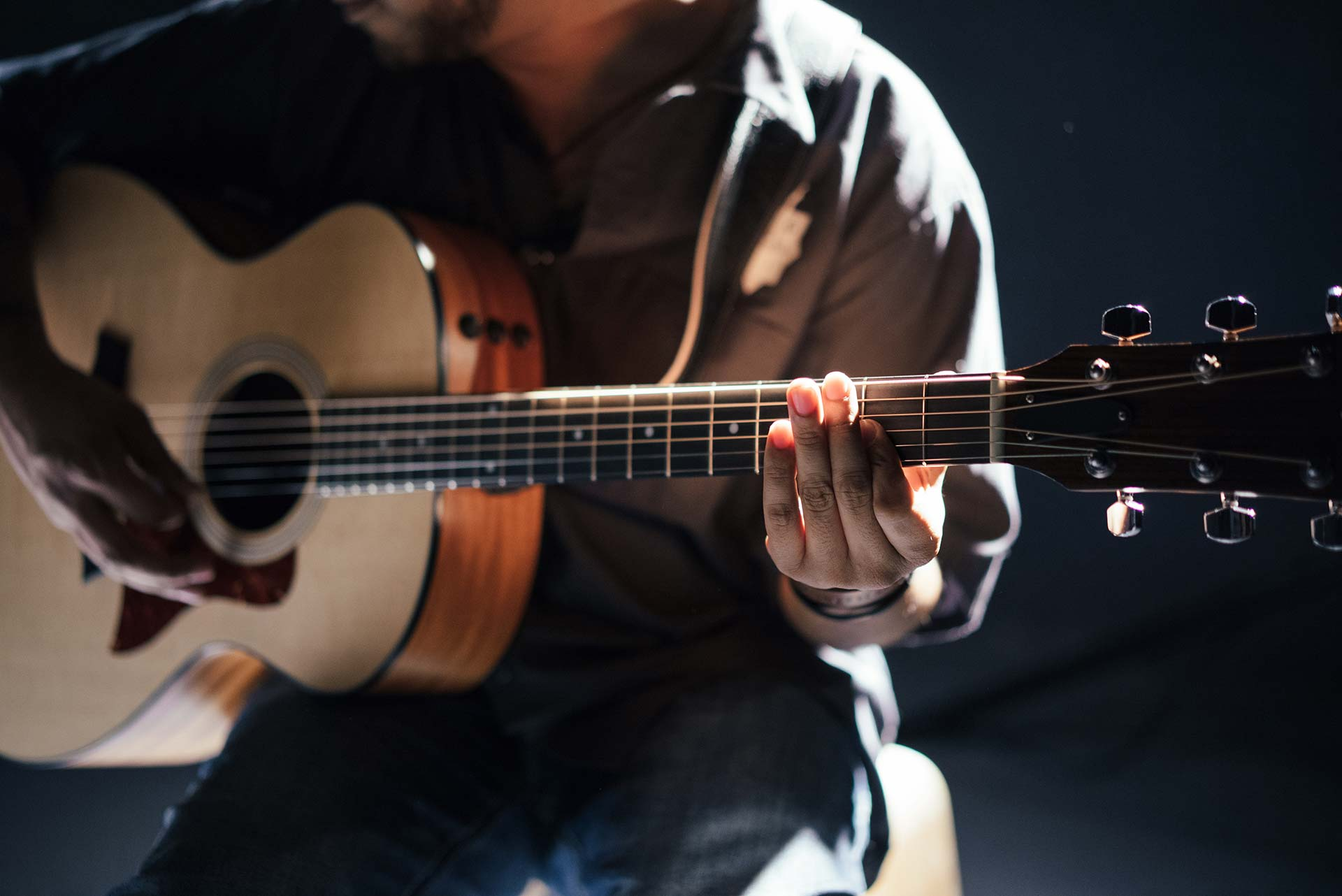 man holding acoustic guitar