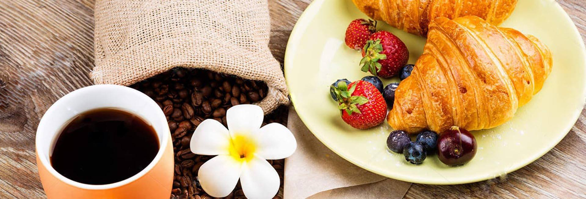 strawberries and blueberries with breads on white ceramic plate near coffee