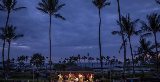people dancing on stage near coconut trees at night
