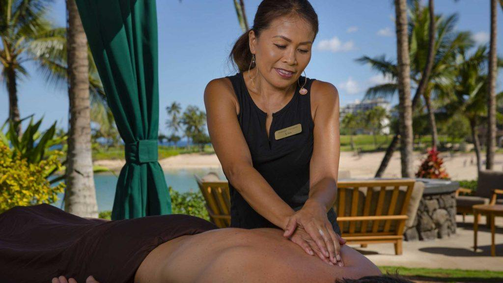woman doing massage beside green curtain during daytime