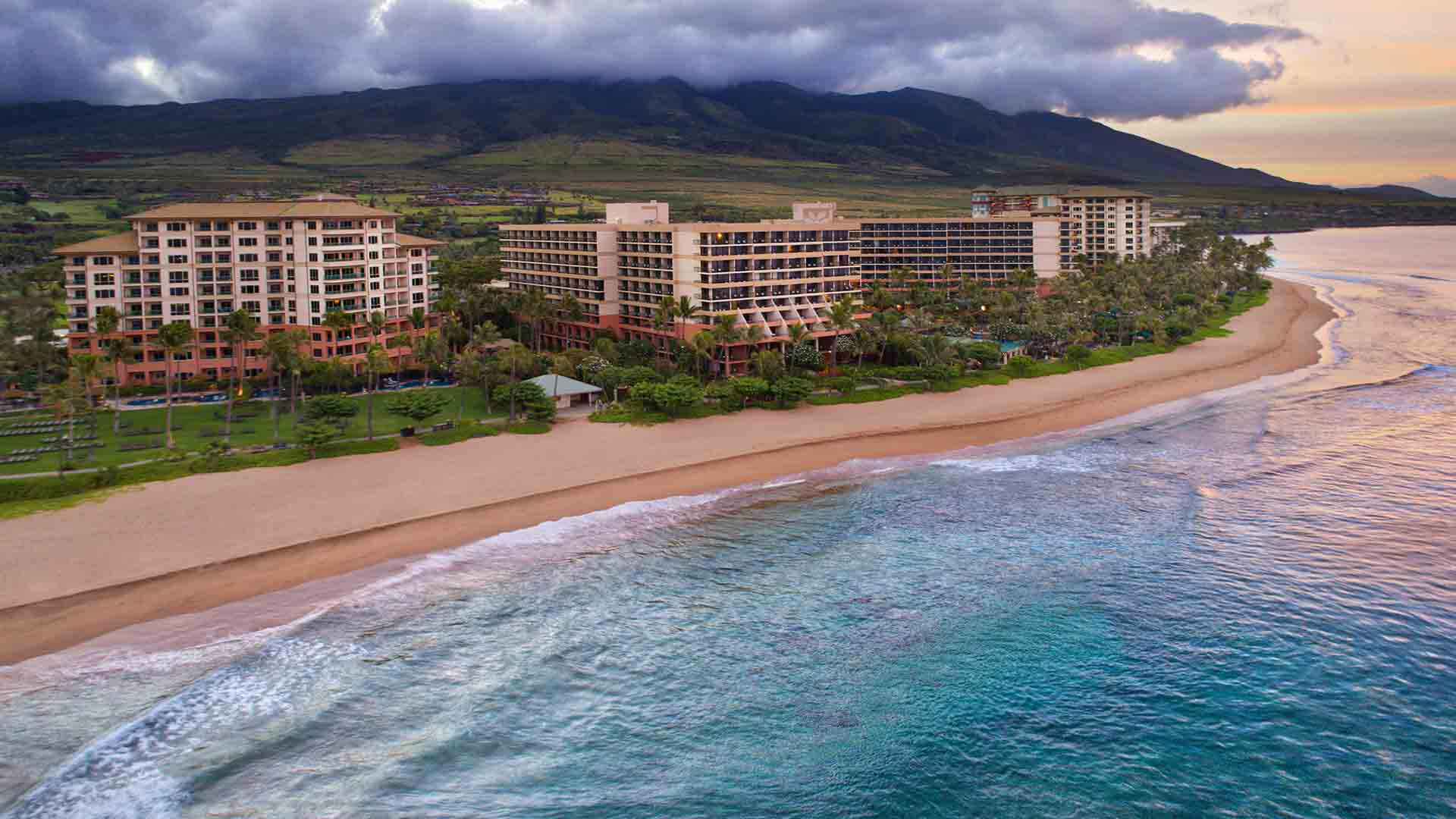 exterior aerial shot of luxury maui beachfront hotel with cloud covered mountain in the background