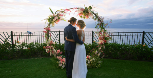 man and woman standing near floral arch and ocean water during daytime
