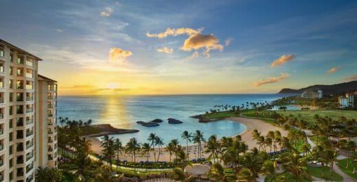 a hawaii resort with a large clamshell-shaped beach surrounded by palm trees and the sun setting over the ocean.